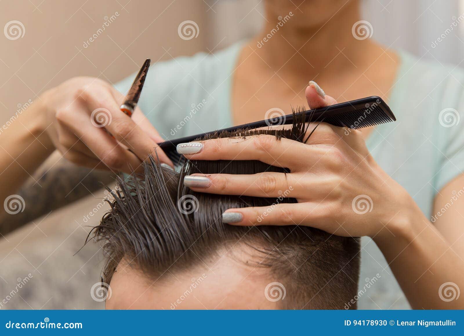 Schließen Sie oben von den Händen des jungen Friseurs Haarschnitt machend dem attraktiven Mann im Friseursalon