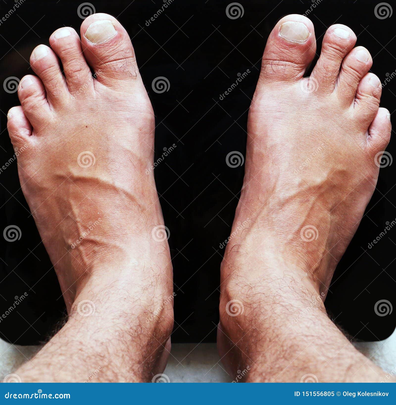 Schließen Sie oben von den männlichen Füßen auf Glasskalen des schwarzen digitalen Bodens
