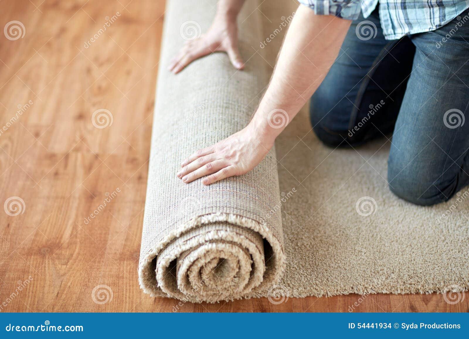 Fußboden Teppich Xl ~ Schließen sie oben von den manneshänden die teppich rollen