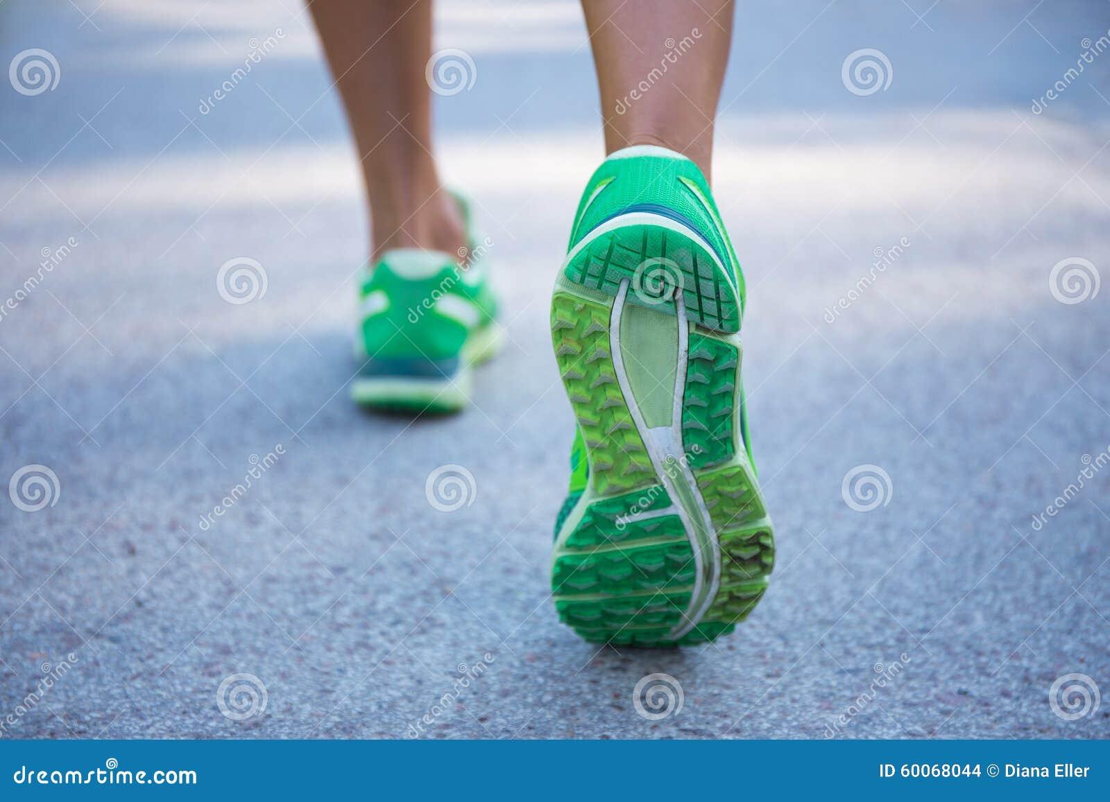 Schließen Sie oben von den weiblichen Beinen, die auf Straße laufen