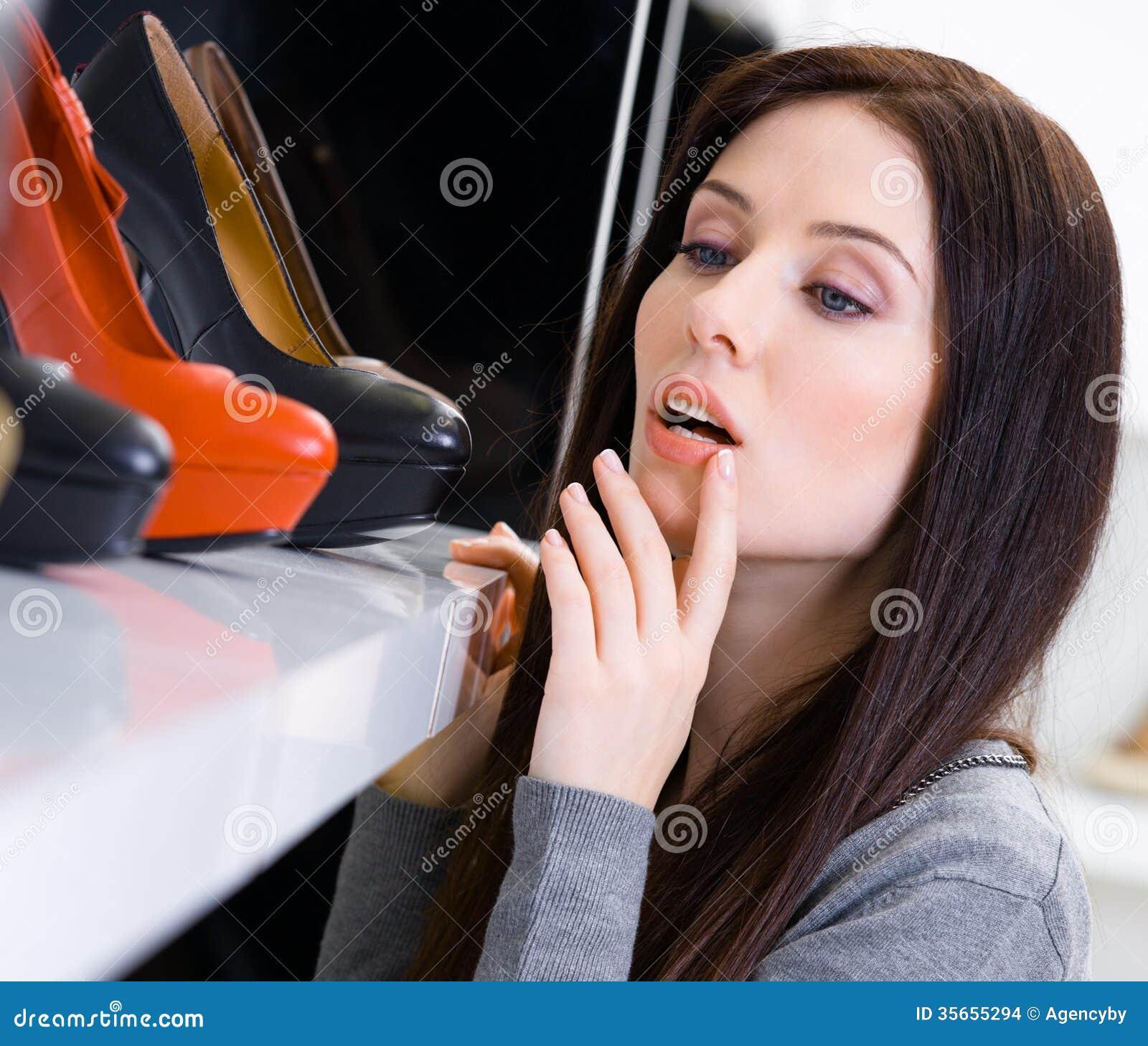 Schließen Sie oben von der Frau, die ein Paar Schuhe wählt