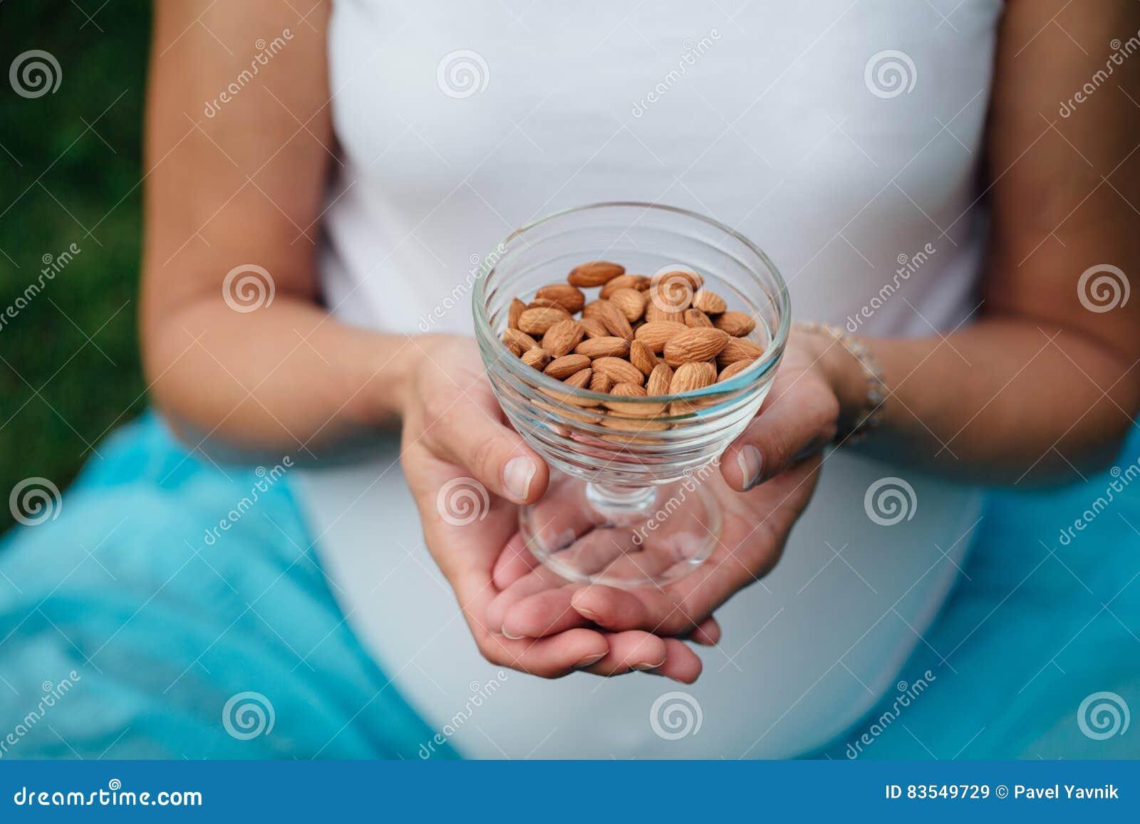 Schließen Sie oben von der Frau, die Glasschüssel mit Mandeln nuts hält