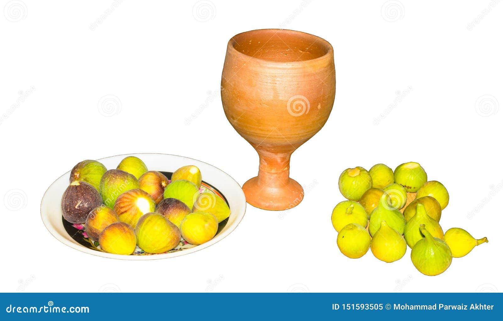 Schließen Sie oben von der frischen Feigenfrucht in einer Platte mit dem lokalisierten Lehmglas