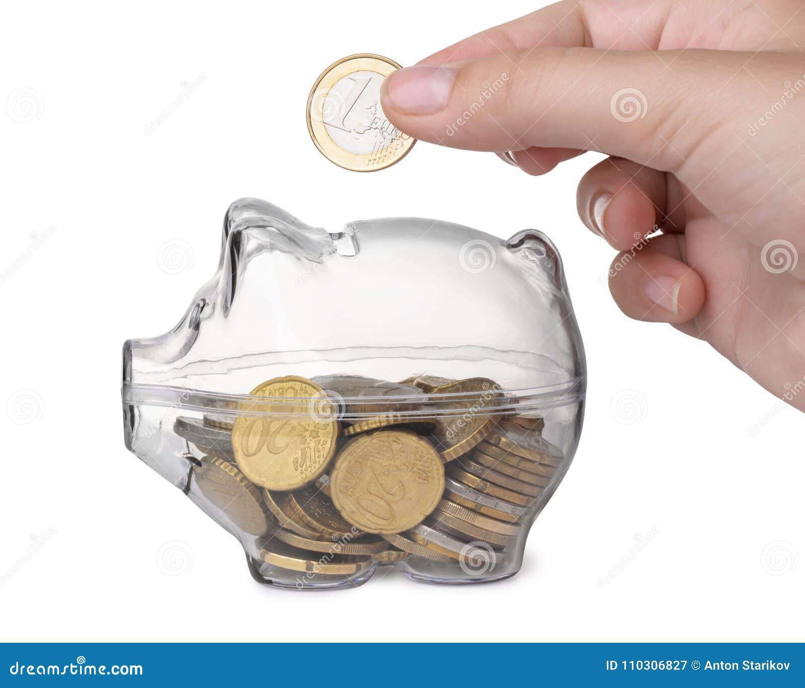 Schließen Sie oben von der Hand, die Münze in Sparschwein setzt