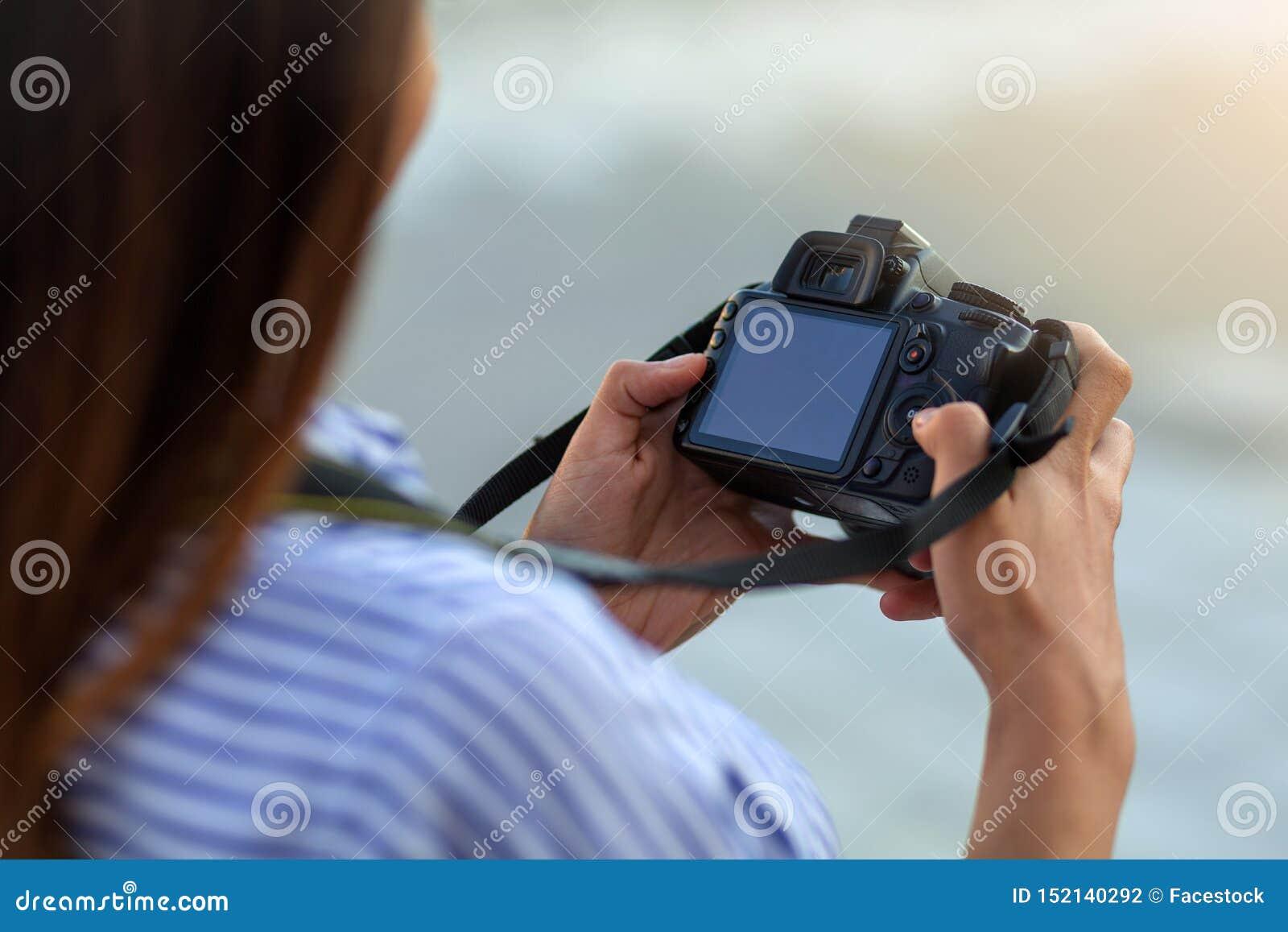 Schließen Sie oben von der jungen Frau mit der Kamera, die Schirm betrachtet