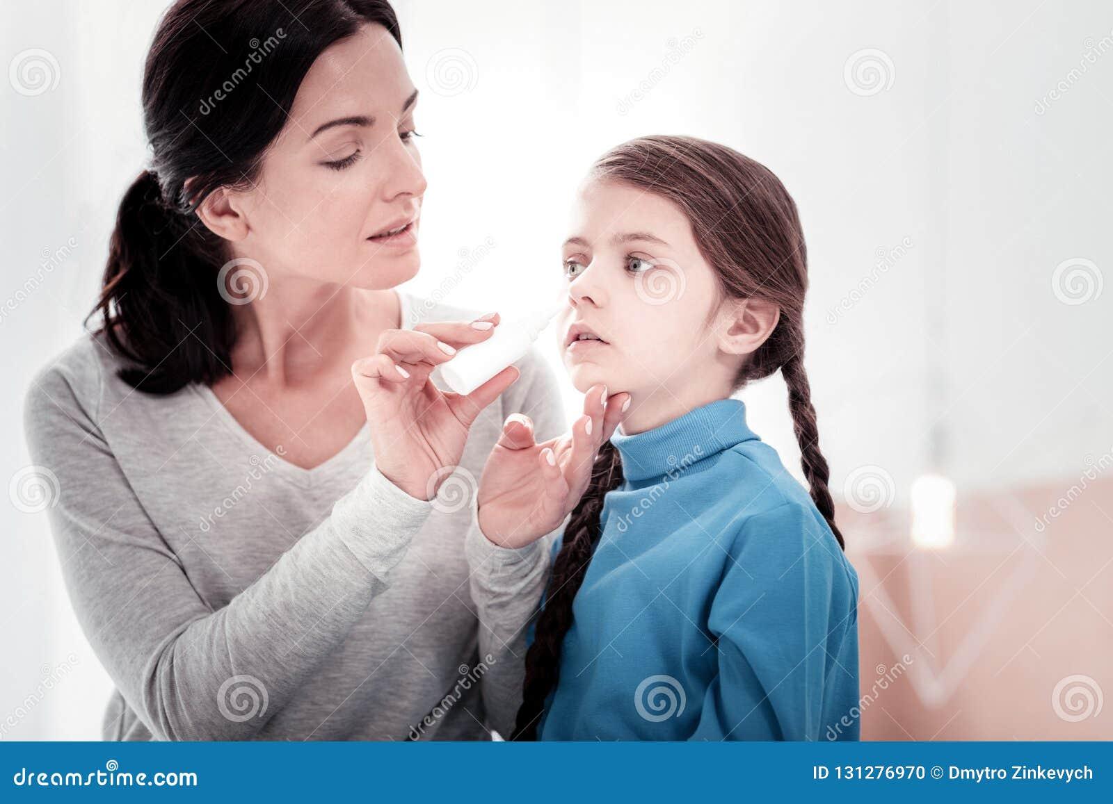 Schließen Sie oben von der jungen Mutter, die ihre Töchter tropft, riechen