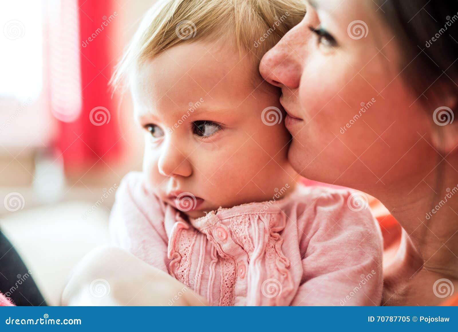 Schließen Sie oben von der Mutter, die ihre nette Babytochter hält