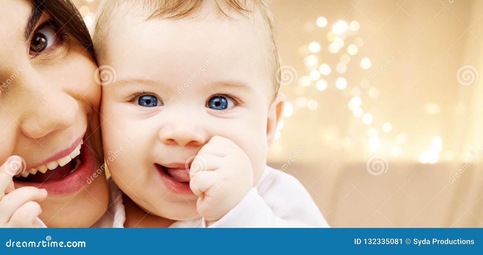 Schließen Sie oben von der Mutter mit Baby über Weihnachtslichtern
