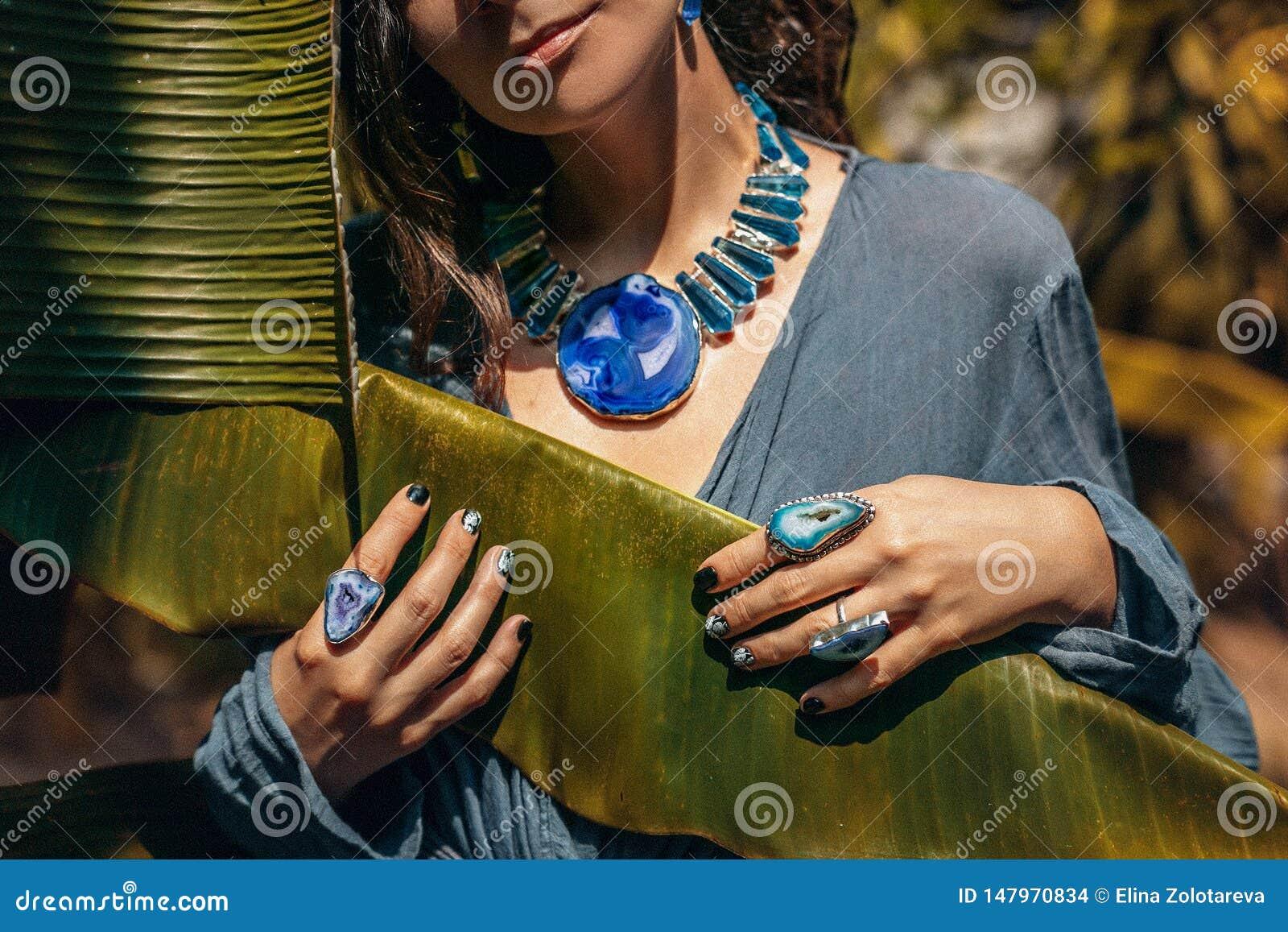 Schließen Sie oben von Edelsteinsteinschmuck der jungen Frau tragendem draußen