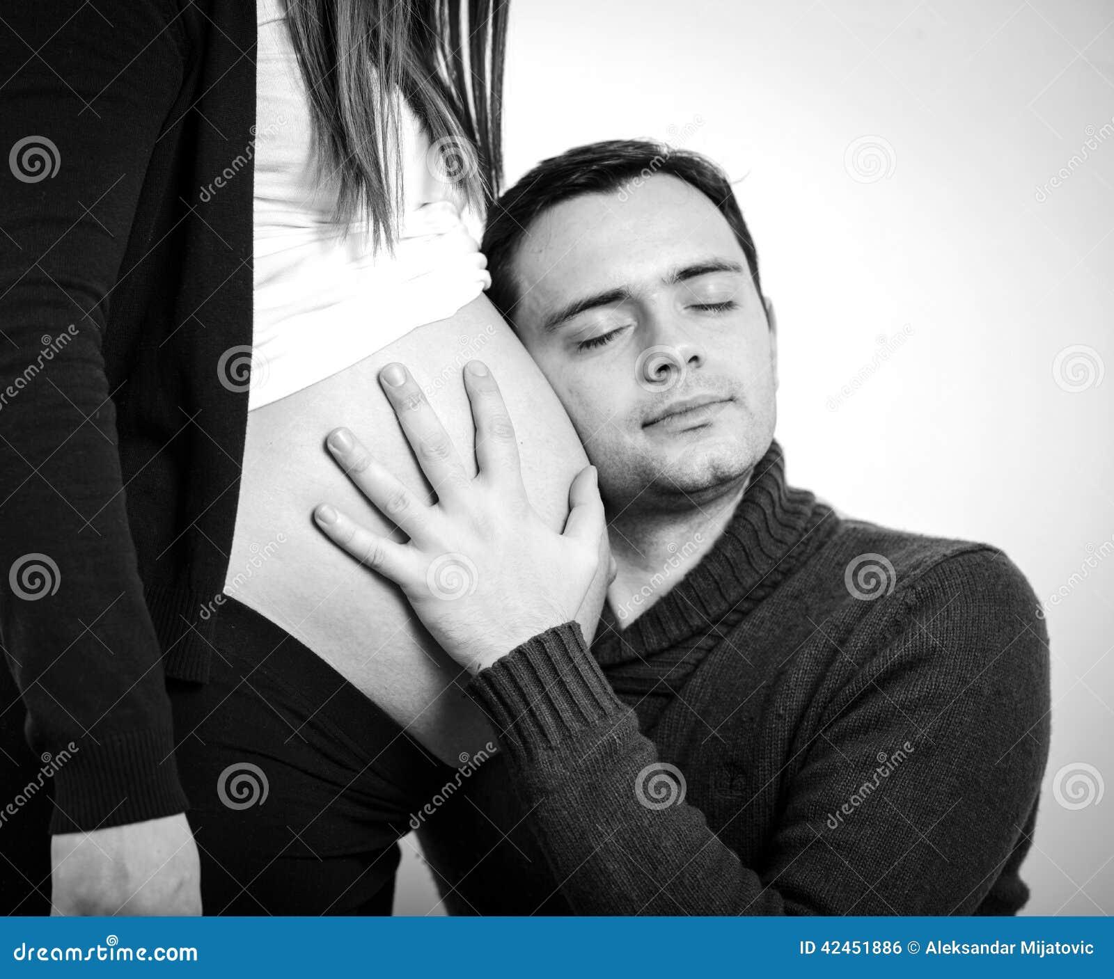 Schließen Sie oben von einem Mann, der den Bauch seiner reizenden schwangeren Frau küsst