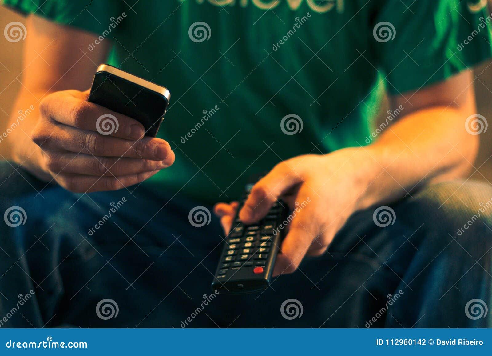 Schließen Sie oben von einem Mann, der einen Handy und eine Fernsehfernbedienung hält