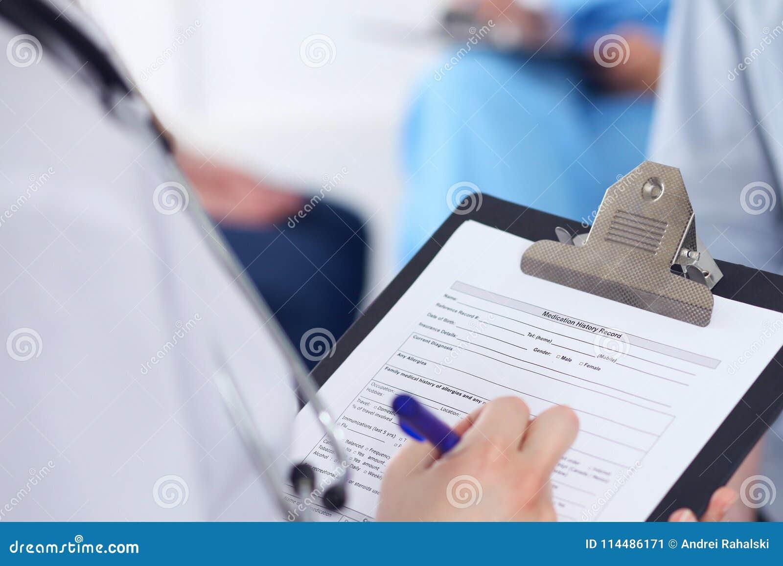 Schließen Sie oben von einer Ärztin, die Anmeldeformular bei der Unterhaltung mit Patienten ergänzt Medizin- und Gesundheitswesen