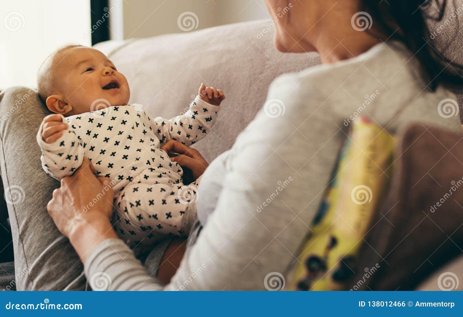 Schließen Sie oben von einer Mutter, die zu Hause mit ihrem Baby sitzt