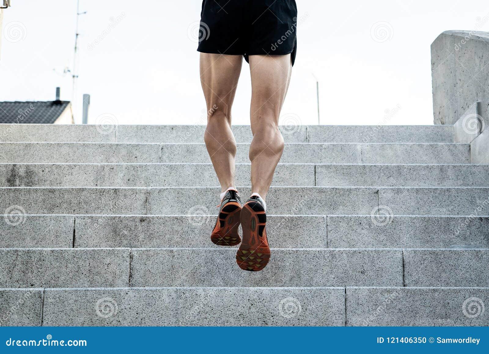 Schließen Sie oben von laufenden Beinen des Mannes bei Sonnenuntergang auf einer Landstraße