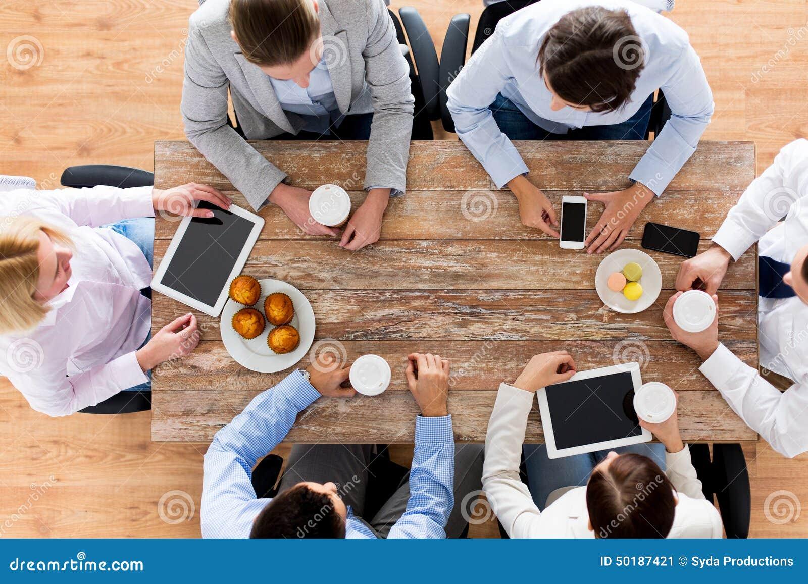 Schließen Sie oben von trinkendem Kaffee des Geschäftsteams auf dem Mittagessen