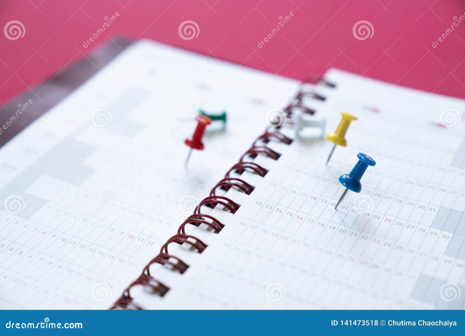 Schließen Sie oben vom Stift vom Kalender auf dem roten Hintergrund