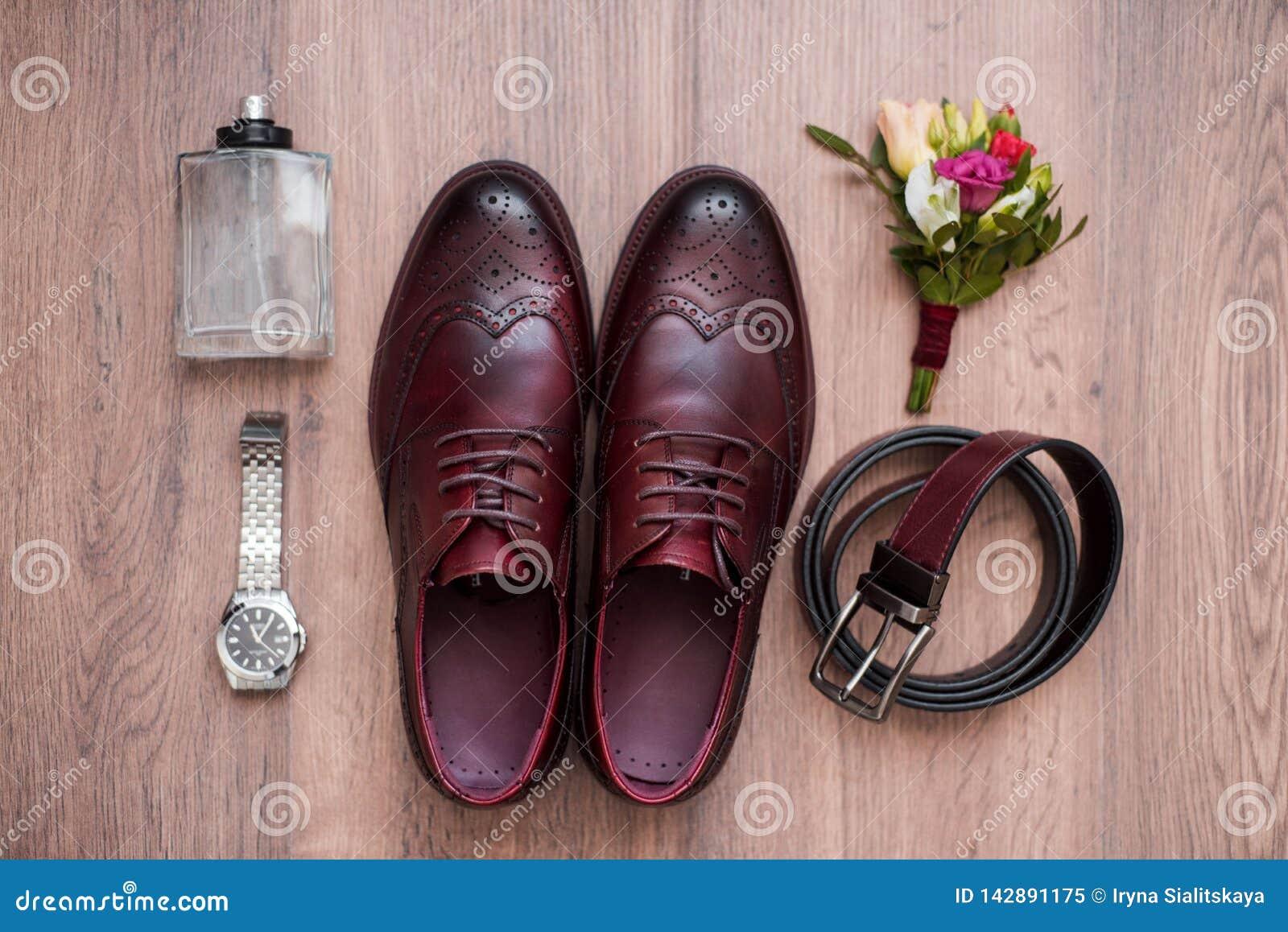 Schlie?en Sie oben vom Zubeh?r des modernen Mannes Schwarzer bowtie, Lederschuhe, Gurt und Blume Boutonniere auf wei?em h?lzernem