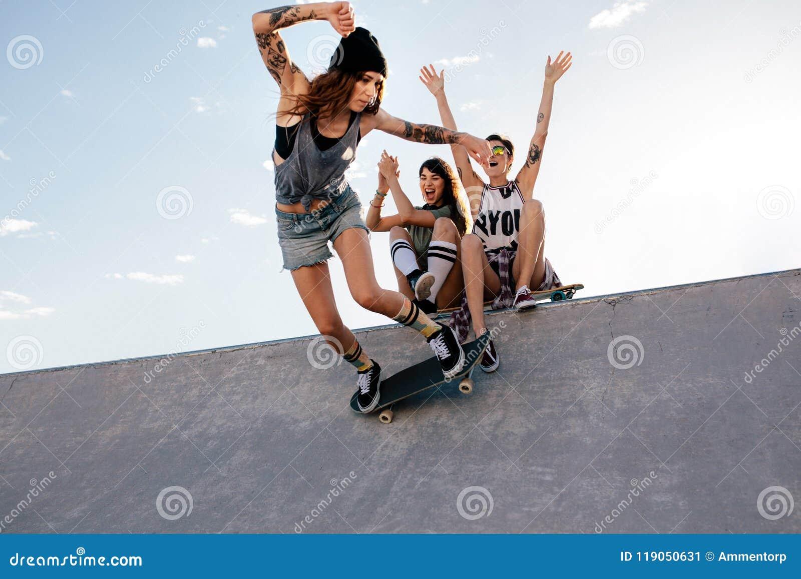 Schlittschuhläufermädchen fährt auf Skateboard am Rochenpark