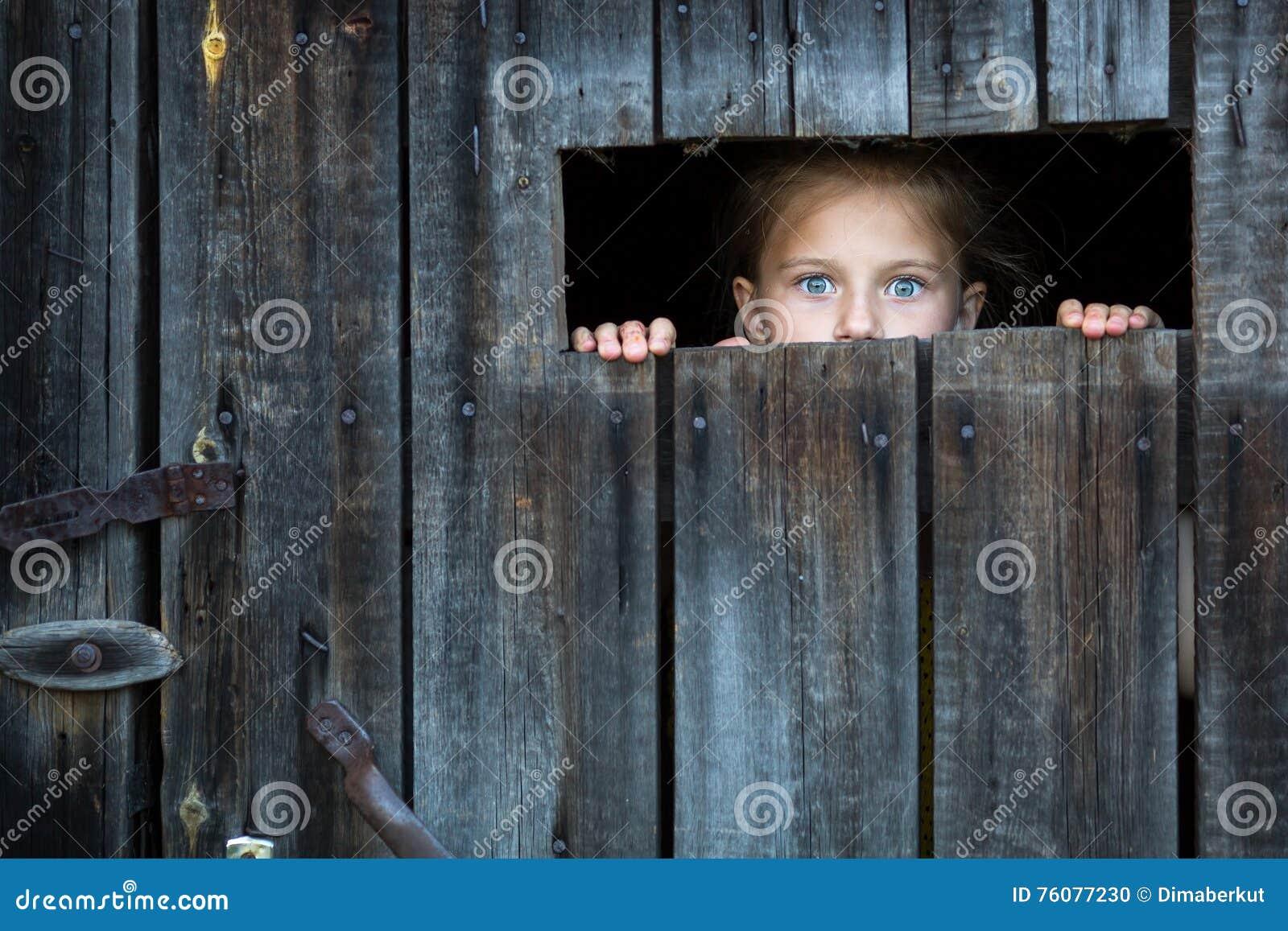 Schloss das Kind schaut besorgt durch den Sprung in der Scheunentür zu schrecken