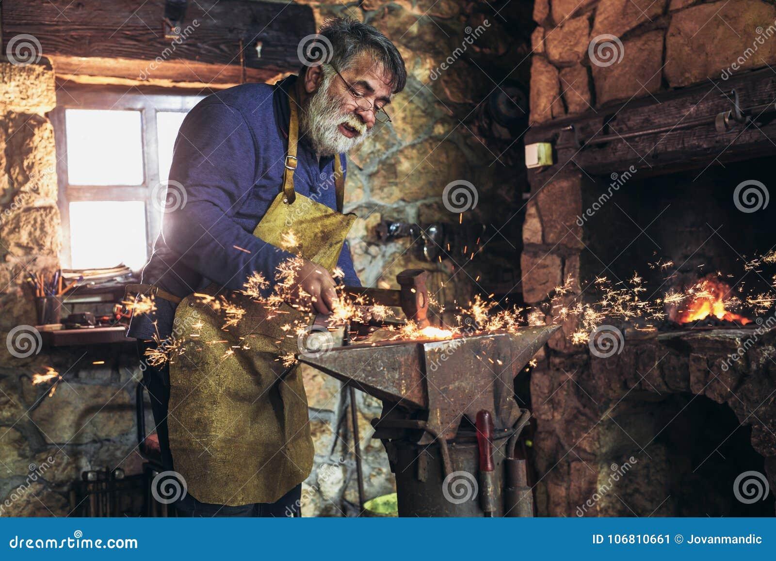 Schmied, der manuell herein das flüssige Metall auf dem Ambosse schmiedet