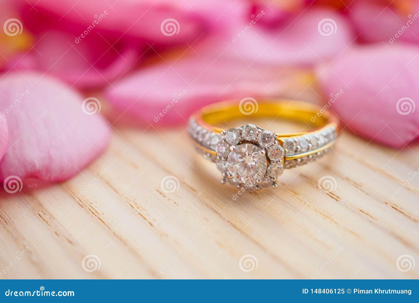 Schmuckdiamantring auf h?lzerner Tabelle mit sch?nem rosa Hintergrund des rosafarbenen Blumenblattes