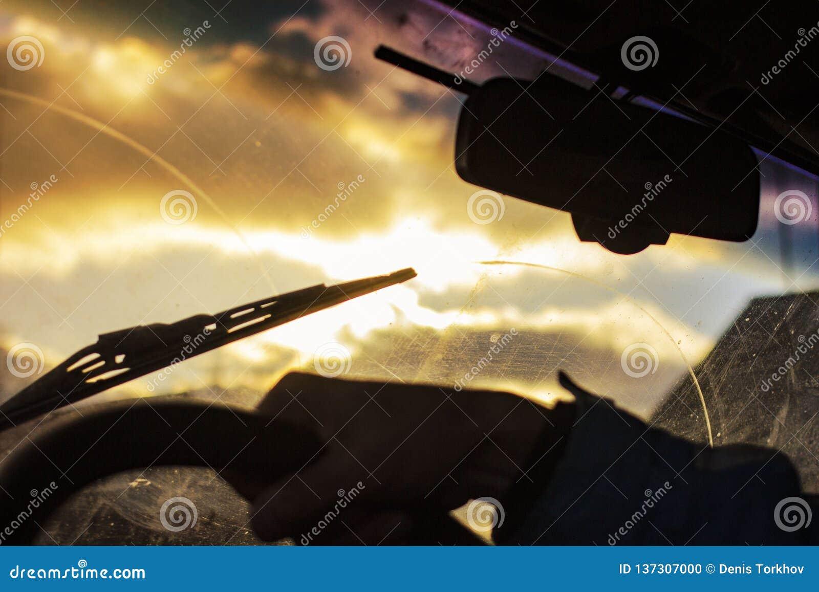 Schmutzige Autowindschutzscheibe mit dem enthaltenen Glasreiniger, in der Großstadtfront und in der Rückseite des Hintergrundes w