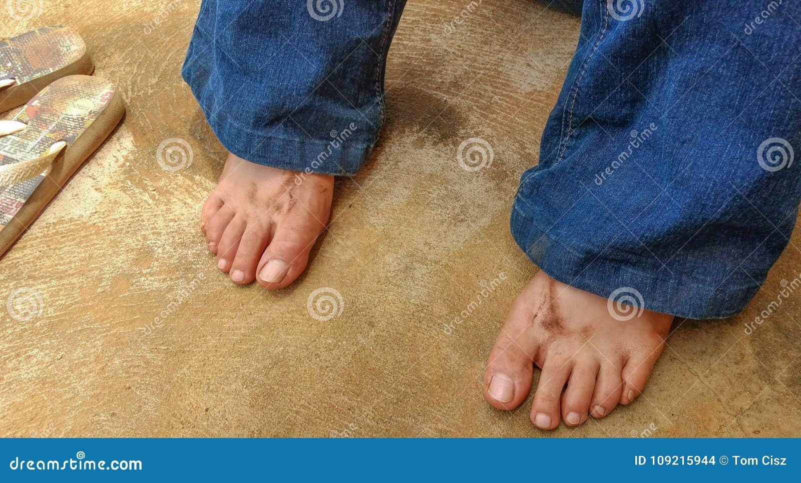 Schmutzige Mädchen ` s Füße, die bei den Flipflops nahe bei ihr nachdem dem Arbeiten im Garten liegen