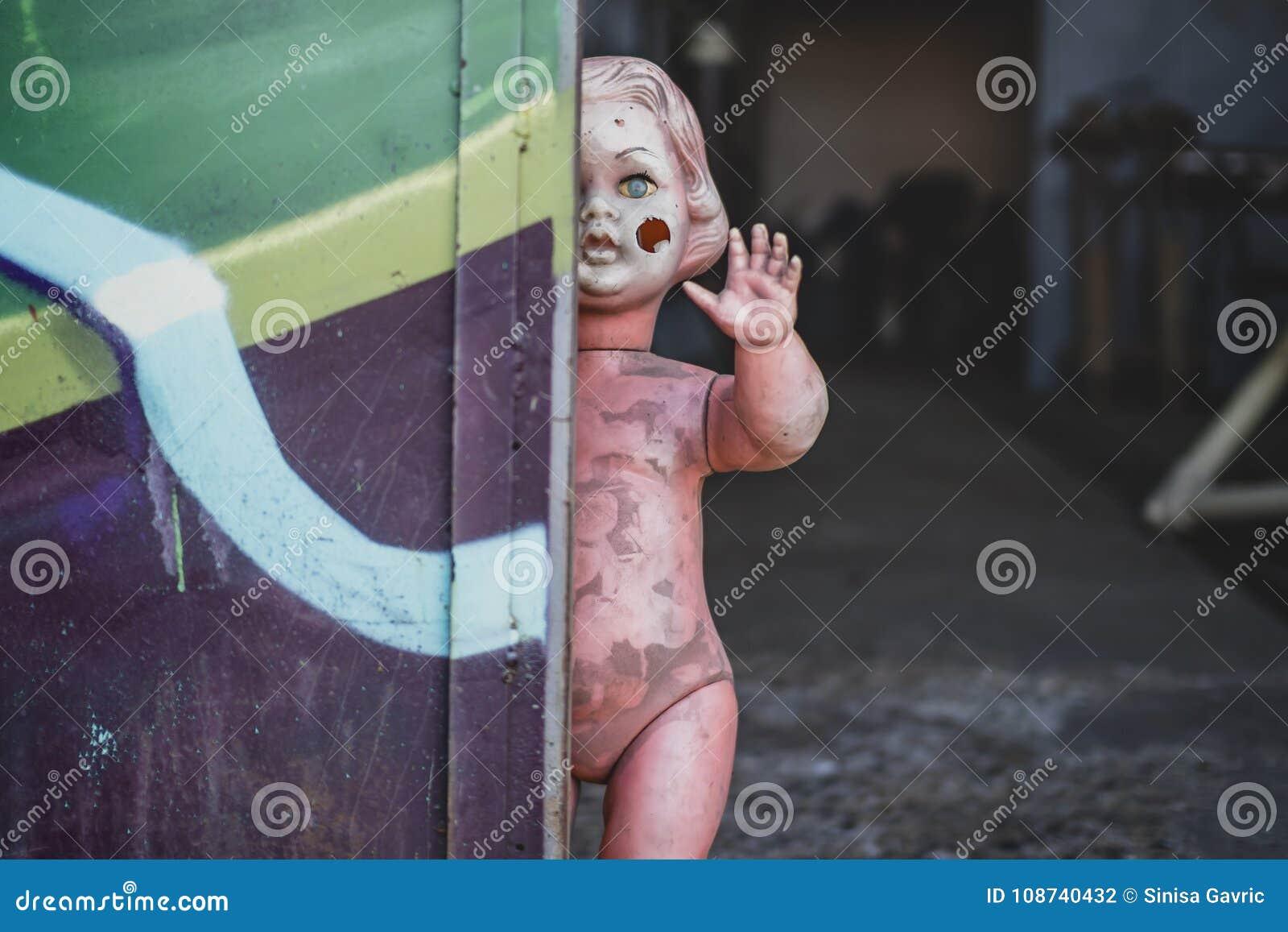 Schmutziges nacktes Plastikbaby - Puppe, welche die Tür am schauenden Metallshop unheimliches und gejagtes Spinnen bereitsteht