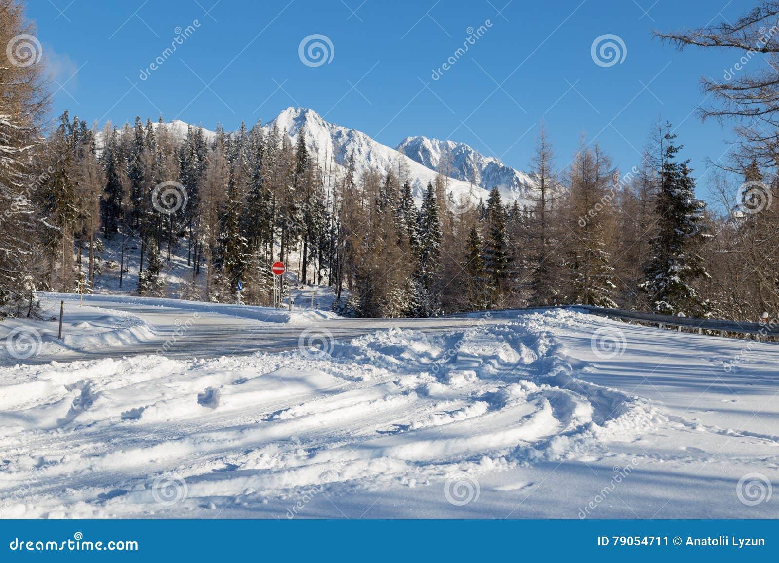 Schneebedeckte Straße des Winters mit Ansichten von Bergen der schneebedeckten Spitzen