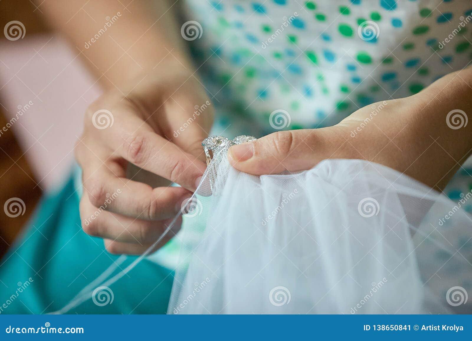 Schneider, der den Schleier einer Braut näht Schließen Sie herauf Hände