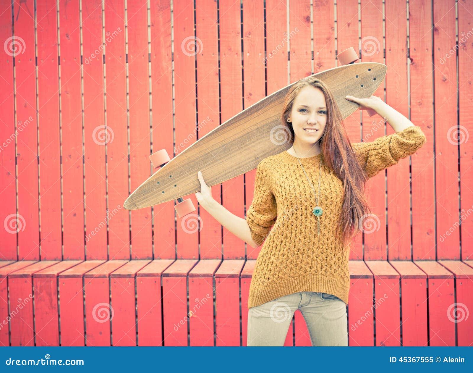 Schönes redheaded mädchen, das ein longboard steht nahe roter wand ...