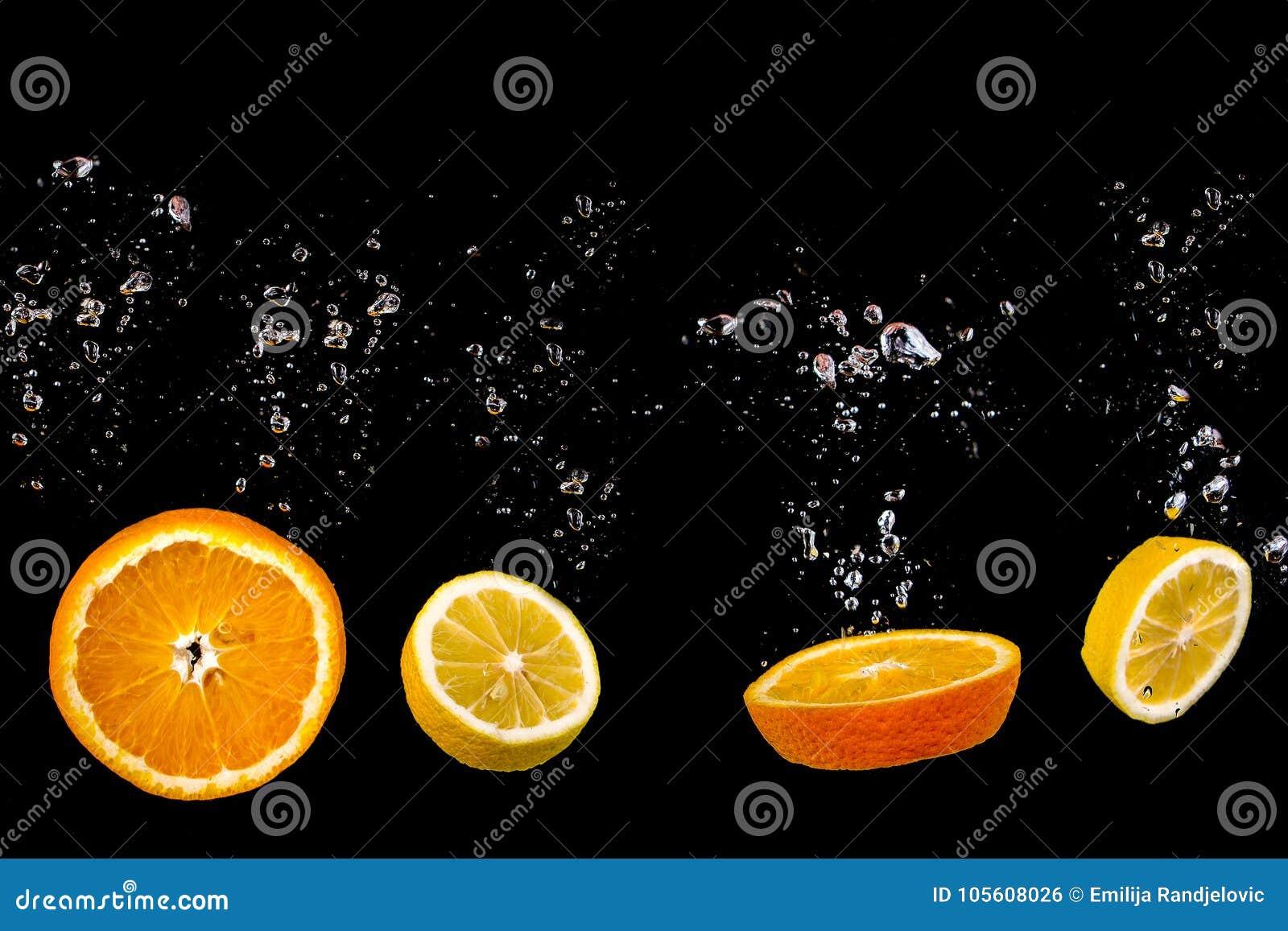 Schnittorangen- und -zitronenflöße auf Wasser mit Blasen, Früchte ist auf einem schwarzen Hintergrund