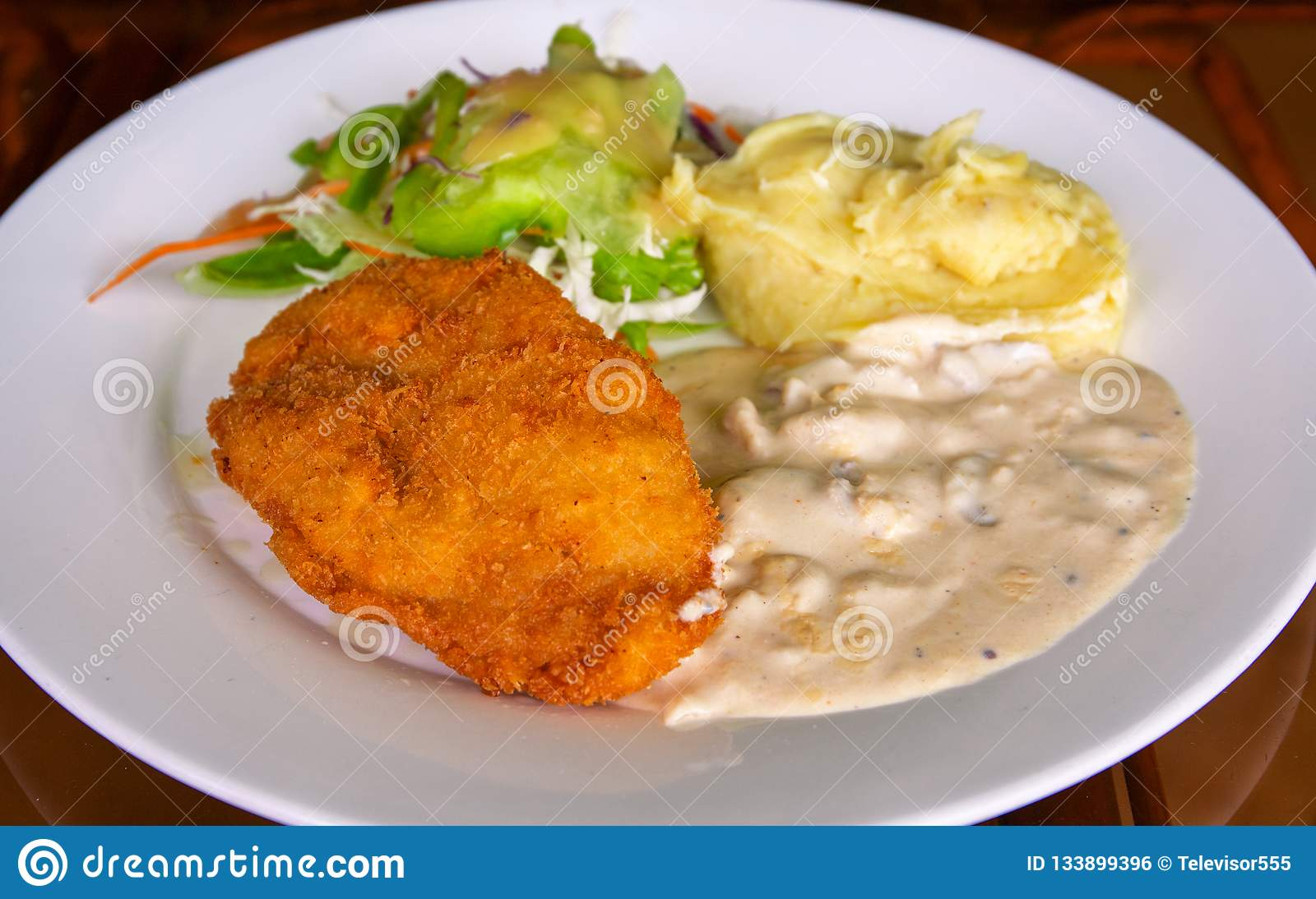 Schnitzel with mashed potato on white plate. Fried chicken cutlet top view photo on wooden table. Tasty lunch served