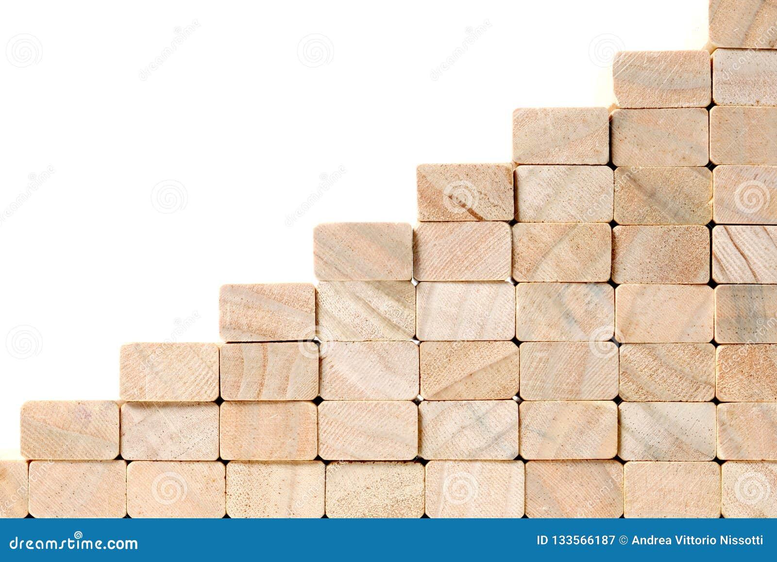 Schodki sukces budowa z drewnianymi blokami na popielatym tle z kopii przestrzenią