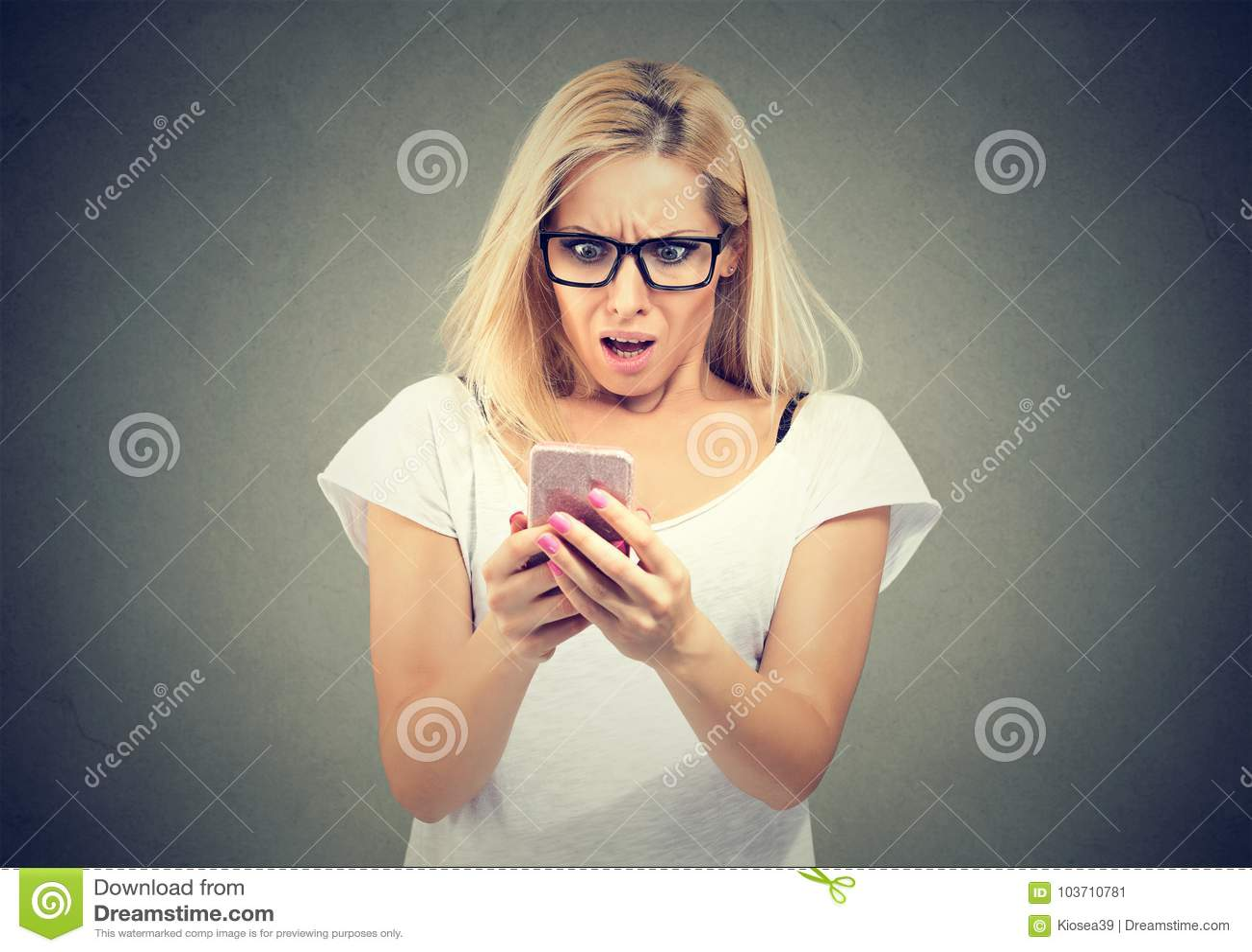 Schokierende Meldung Überraschte Frau des blonden Haares, die Handy hält und entlang er anstarrt