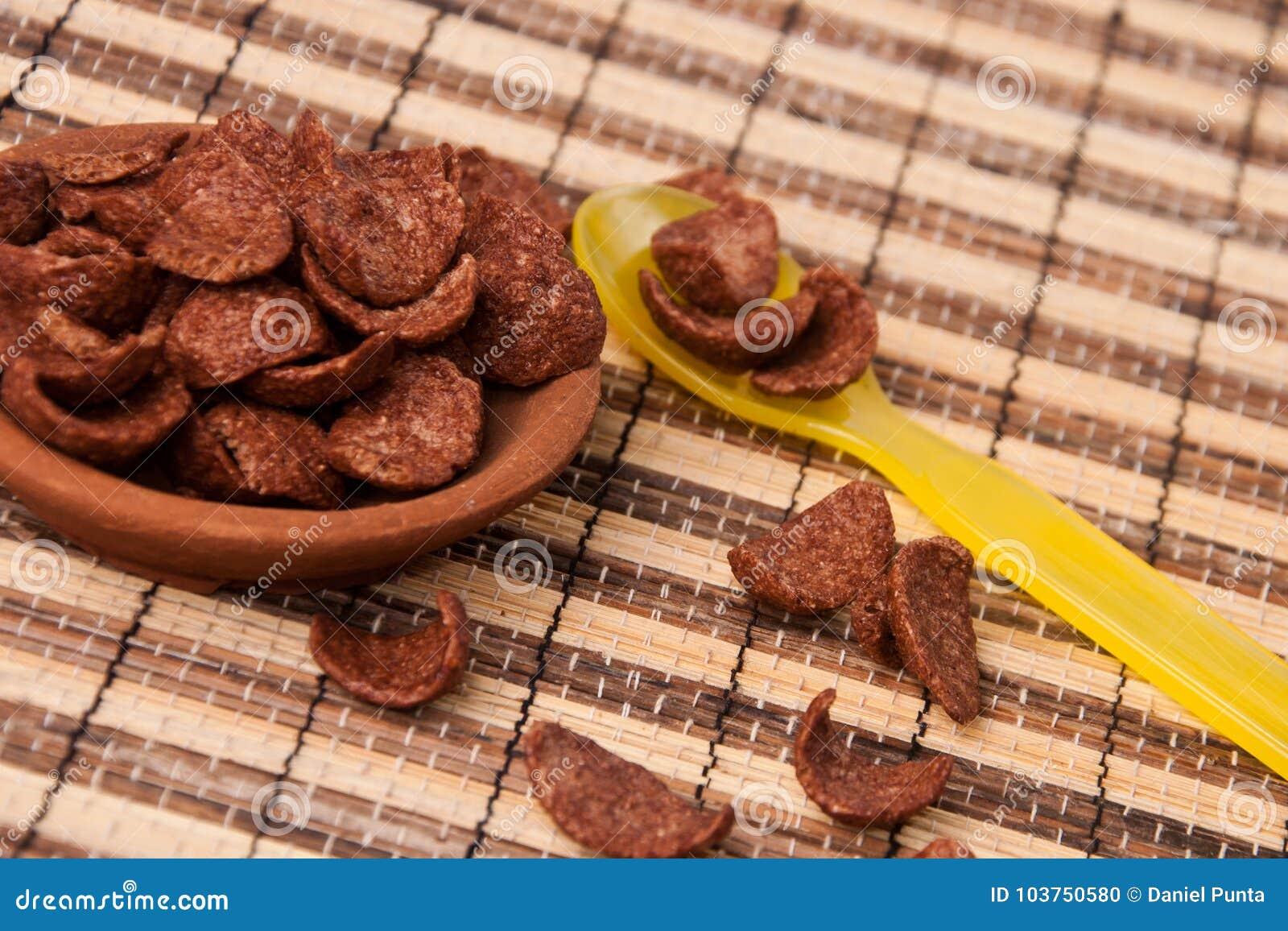 SchokoladenCorn Flakes in der Lehmscheibe und im gelben Plastiklöffel
