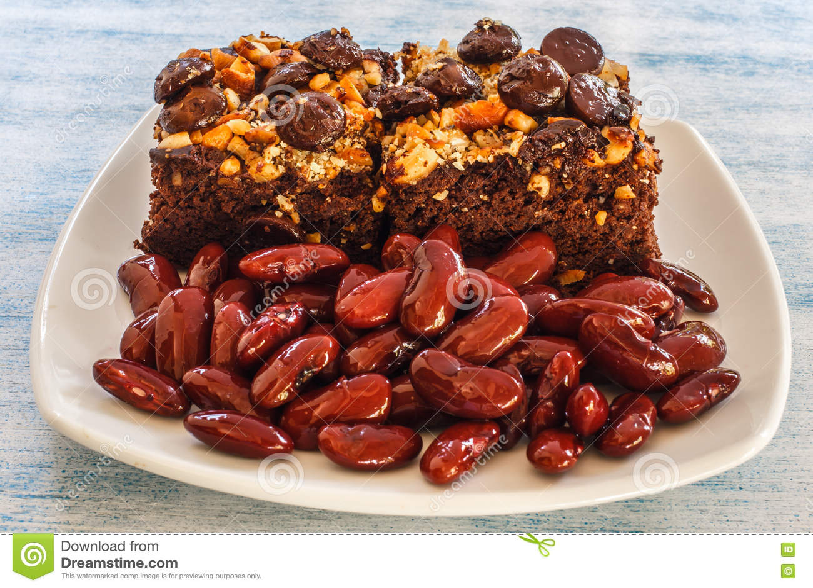 Schokoladenkuchen der roten Gartenbohnen und gekochte rote Bohnen auf blauem hölzernem Hintergrund