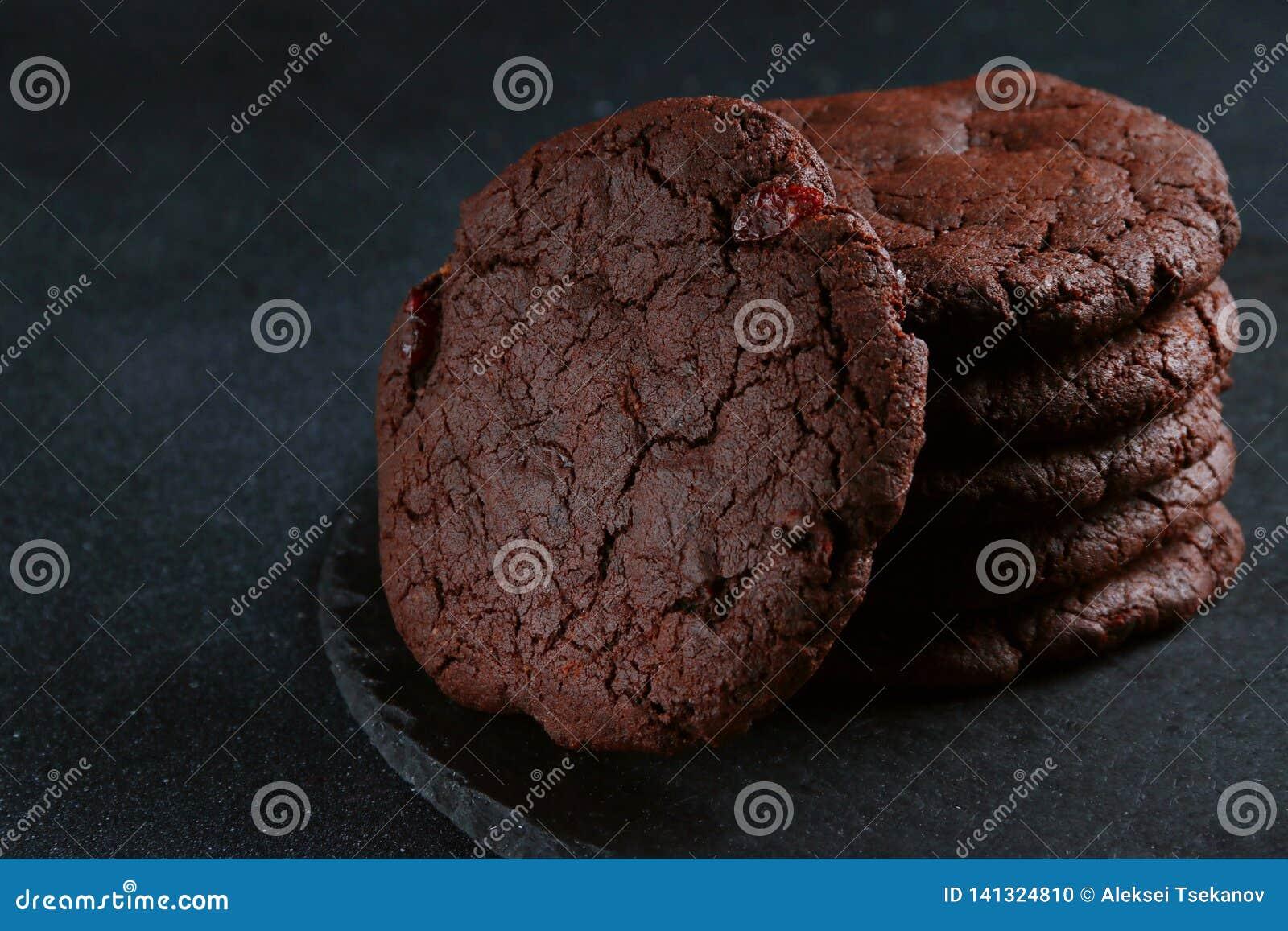 Schokoladenplätzchen auf dunklem Hintergrund Schokoladenkuchenplätzchenstapel