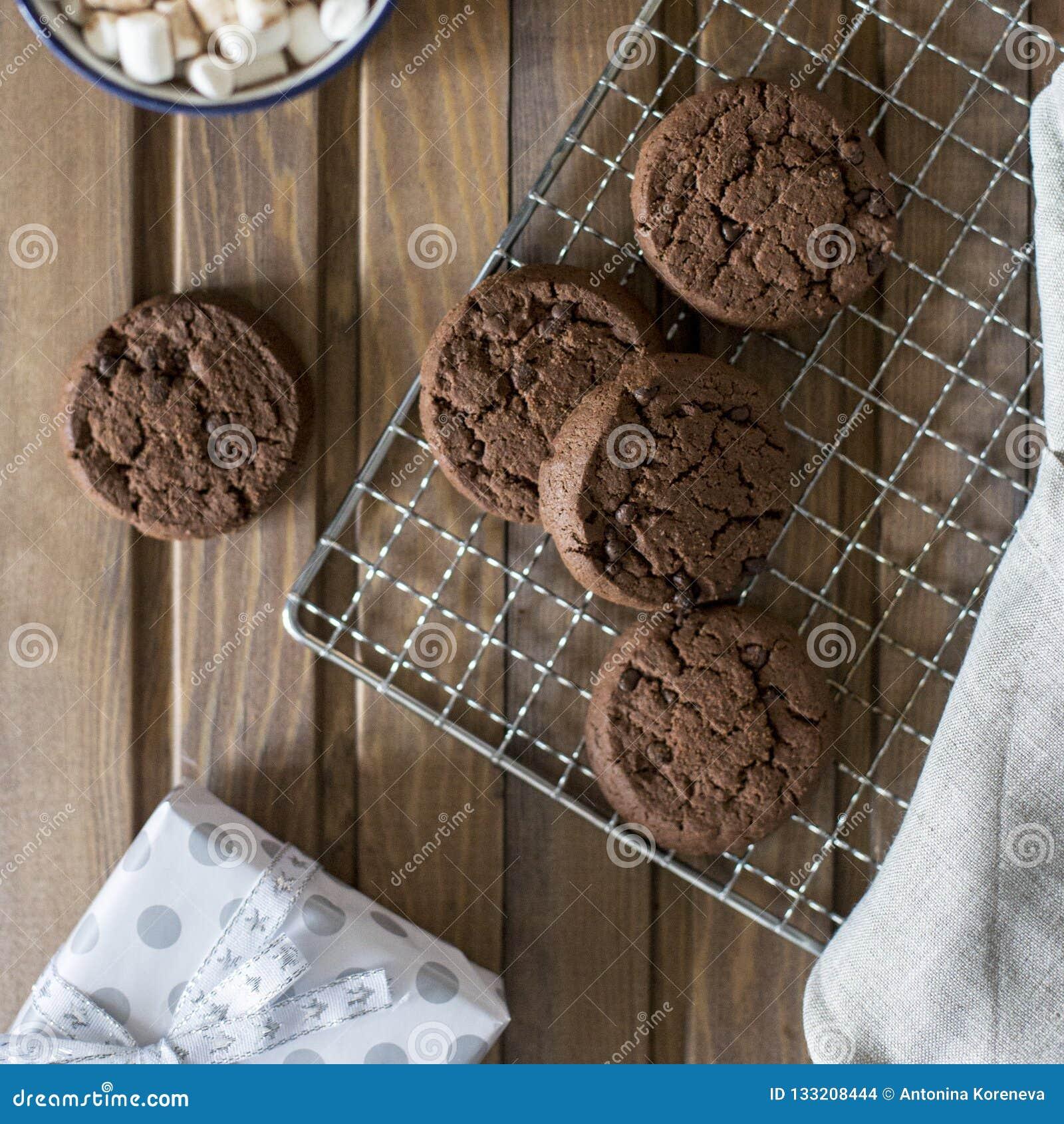Schokoladenplätzchen am Metallgrill, mit Serviette und Schale nahe auf hölzernem Hintergrund