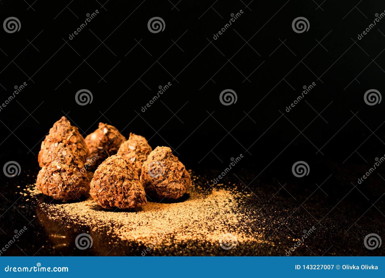 Schokoladentrüffelsüßigkeiten mit Kakaopulver auf einem dunklen Hintergrund