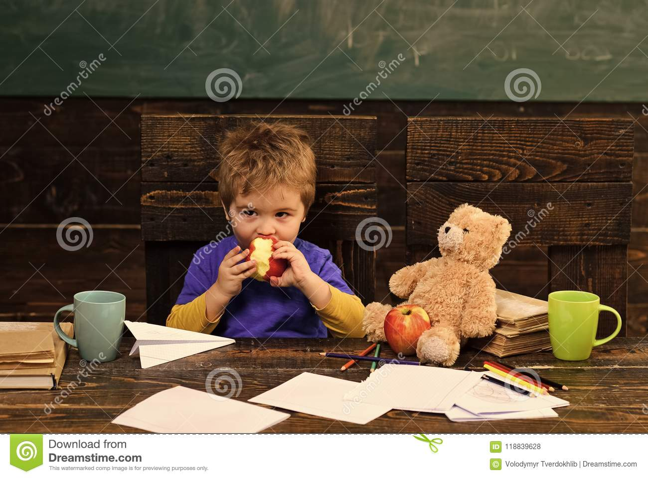 School change. School break. Hungry kid biting apple in classroom. Small boy playing with paper plane and teddy bear