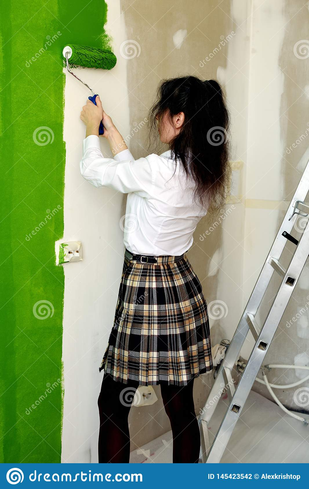School girl is learning how to paint a wall in green with a roller