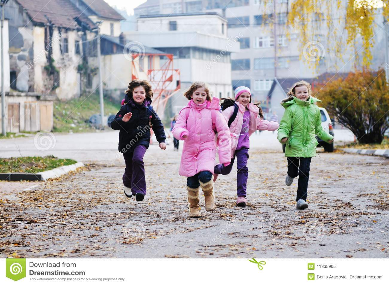 Happy school girls running outdoor at sunny autumn day.