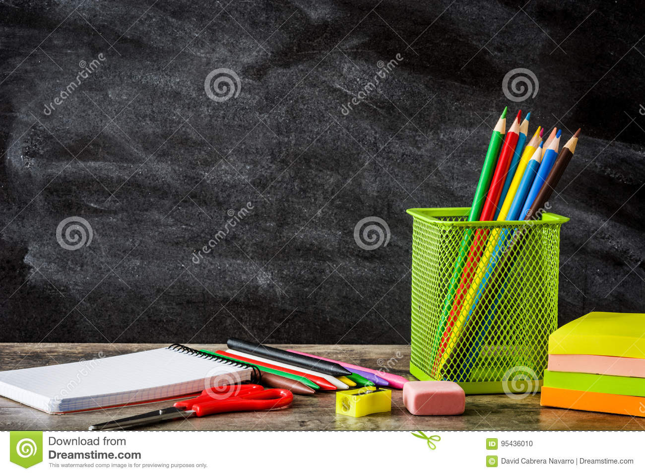 School supplies on wooden table and blackboard background. Back to school concept.