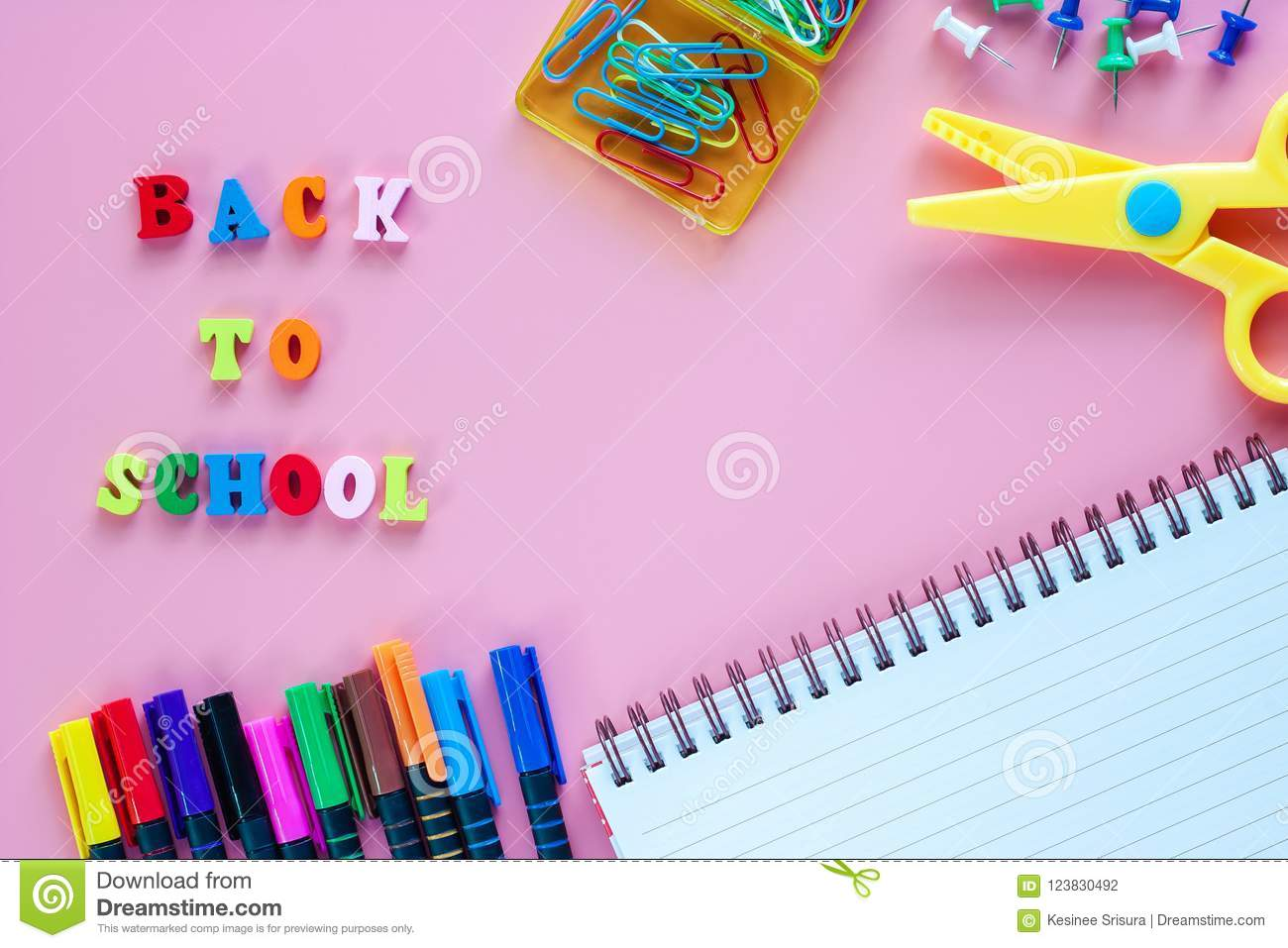 School supplies with wooden text BACK TO SCHOOL on pink background