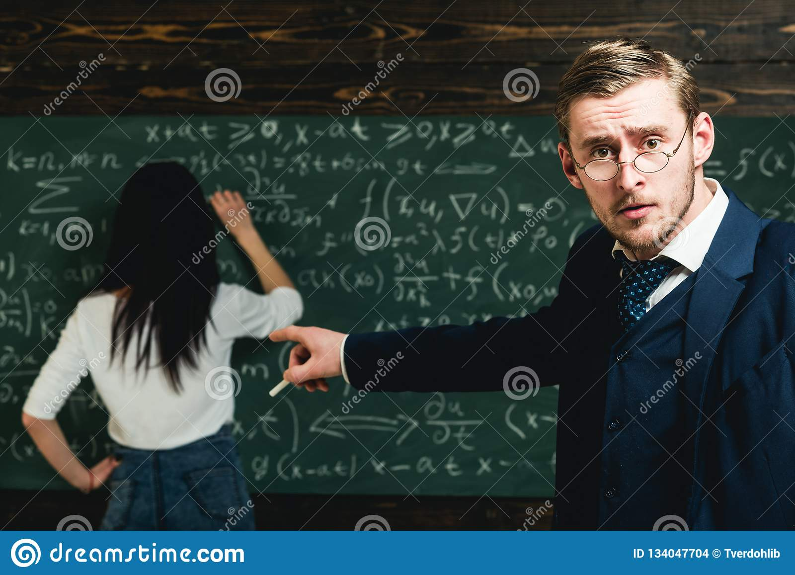 School teacher point finger at student doing sums. School teacher with glasses on smart face