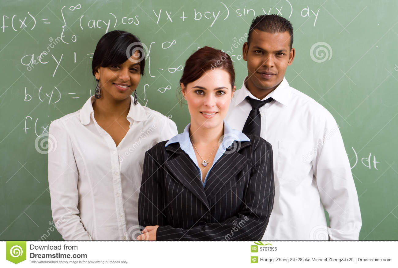 group of three teachers standing in front of a blackboard