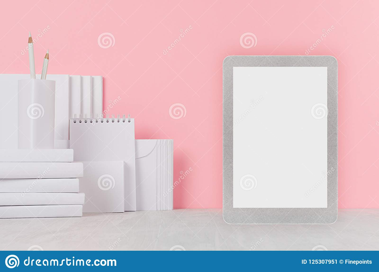 School template - white books, stationery, blank stickers and tablet computer on white desk and soft pink background.