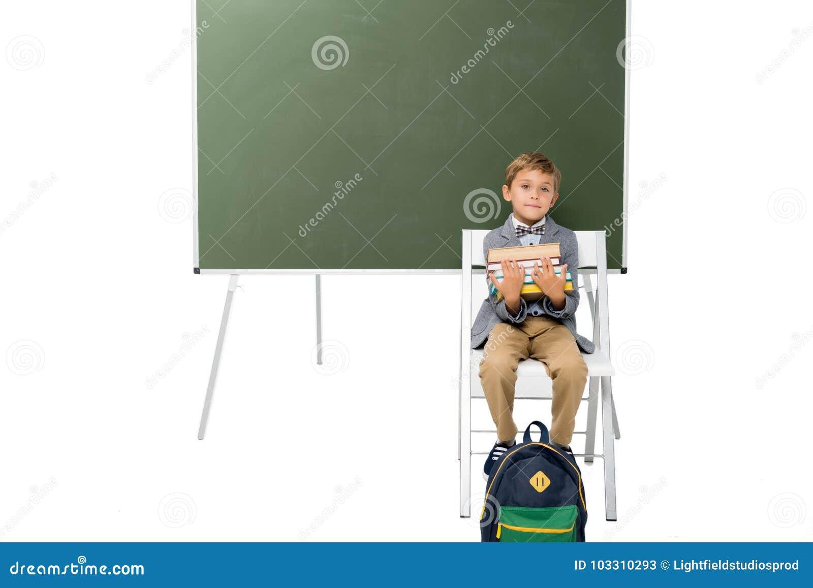 Schoolboy με τη στοίβα των βιβλίων
