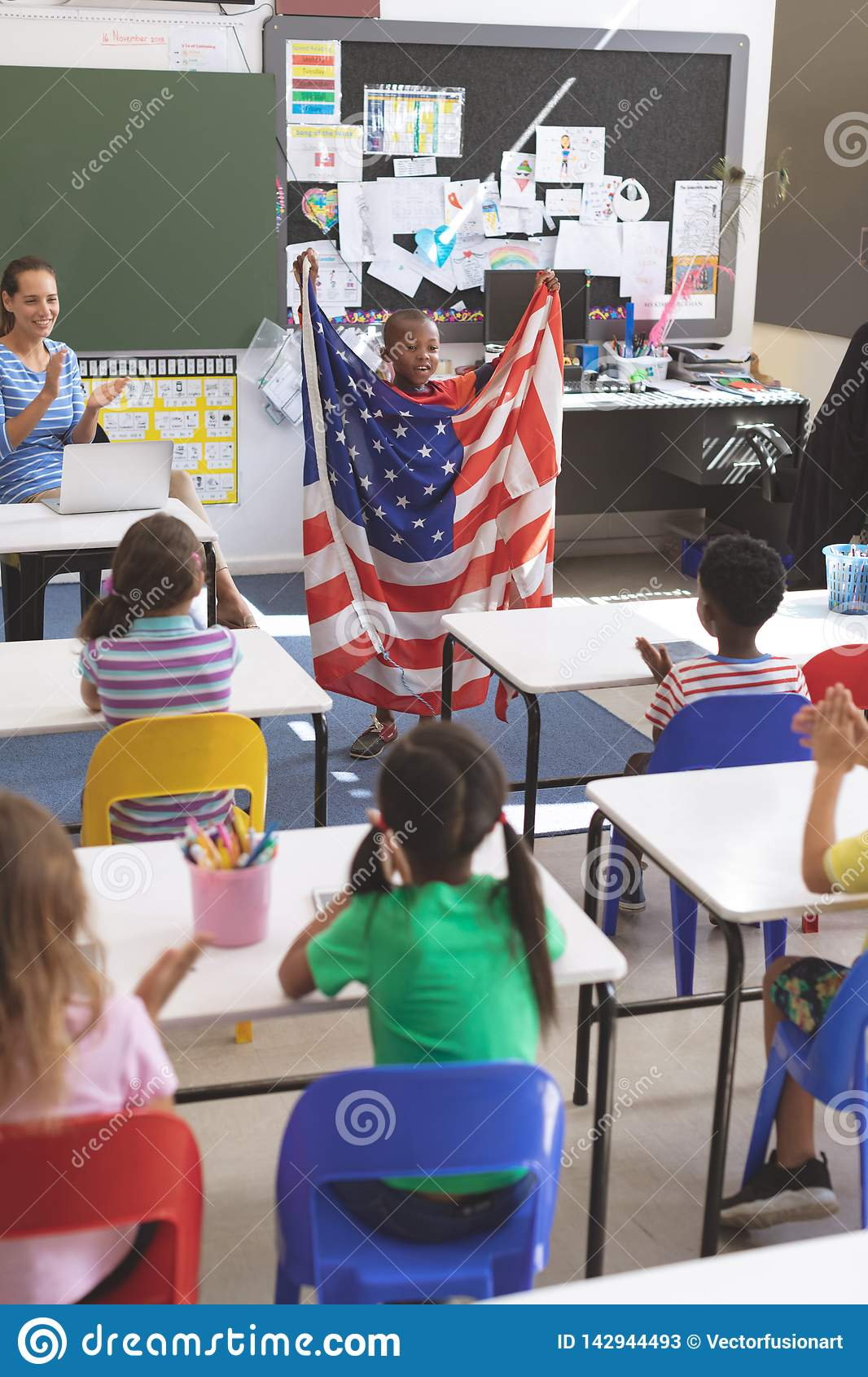 Schoolboy holding an american flag in classroom